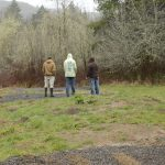three workers decide on cabin sites in the rain