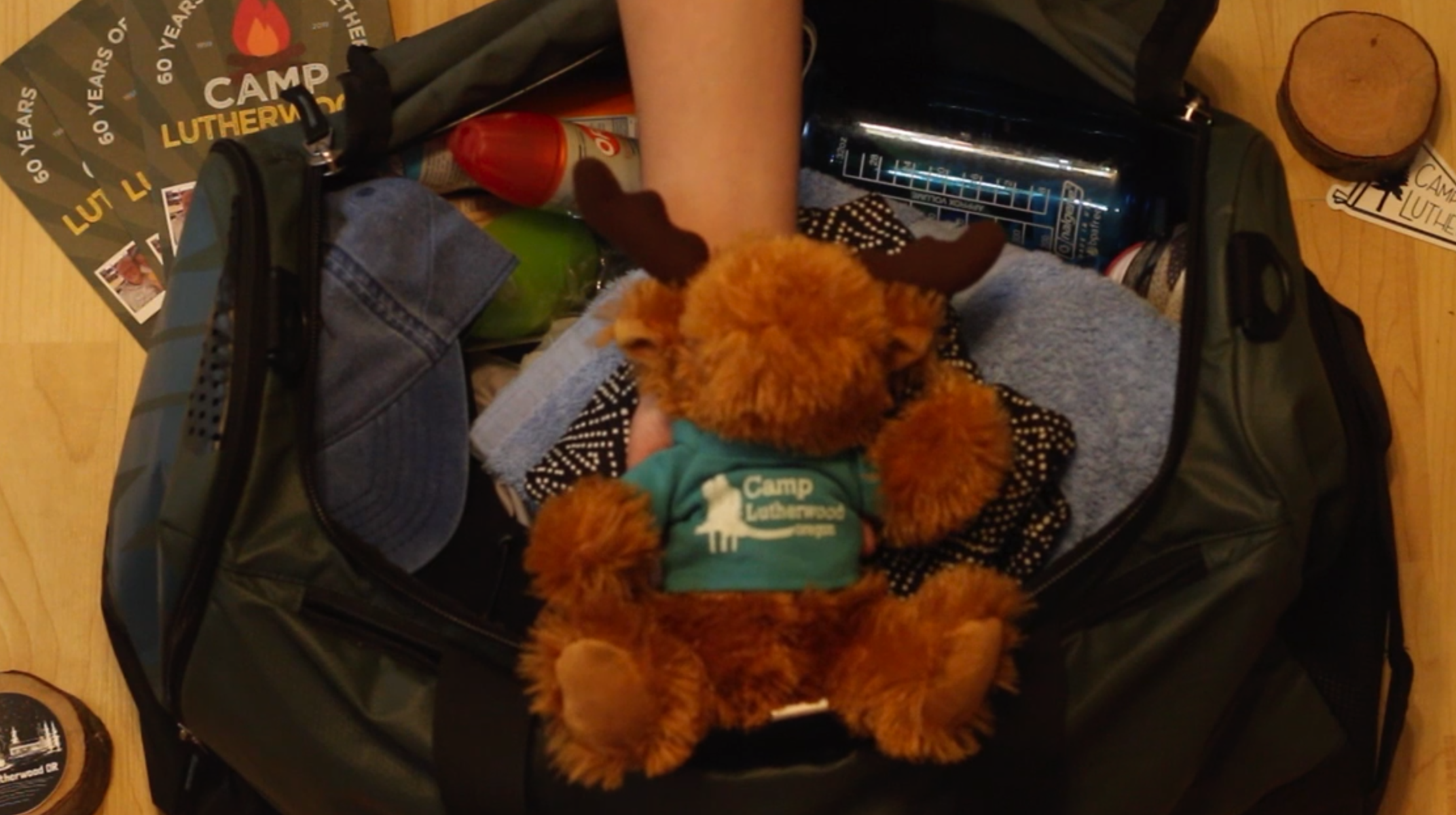 A duffle bag is packed with clothes and other items as a hand holds out a Milo the Moose stuffed animal.